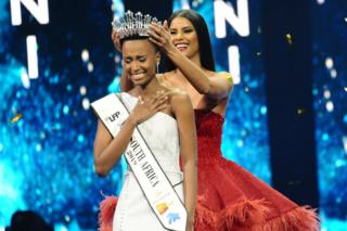 Zozibini Tunzi smiles and clutches her chest as the winner's tiara is laid on her head.