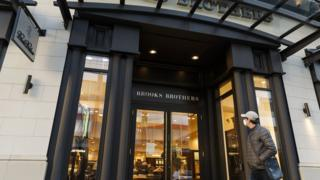 person in mask walks by Brooks Brothers store
