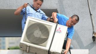 Рабочие устанавливают кондиционер в Шанхае