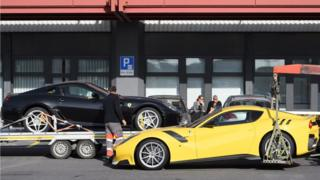 """Two Ferrari sports cars belonging to Teodorin Obiang Nguema, son of Equatorial Guinea""""s President, are being towed off the freight zone by the police at Geneva Airport, in Geneva, Switzerland, 03 November"""