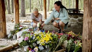 People lay flower bouquets as a makeshift memorial at a forest shelter next to the Haslevej road near Roenne, Bornholm island, Denmark