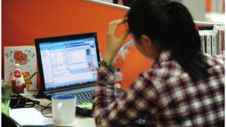 A woman works online in her cubicle at an office in Beijing