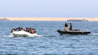 Libyan coast guards escort a boat carrying illegal migrants, who had hoped to set off to Europe with the help of people smugglers from the coastal town of Garabulli, 6 June 2015