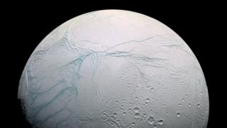 Image of a white ice moon with blue lines streaked across its surface and a small cluster of craters