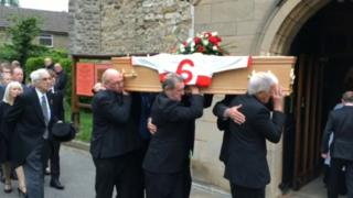 Pallbearers carrying Roger Millward's coffin into a church