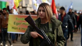A fighter from the Syrian Democratic Forces (SDF) participates in a demonstration in the north-eastern Syrian Kurdish-majority city of Qamishli on December 28, 2018, against threats from Turkey to carry out a fresh offensive following the US decision to withdraw their troops