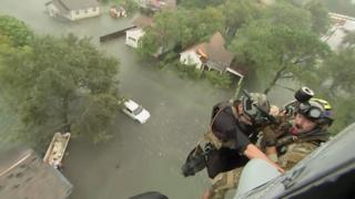 Two rescuers from US Navy Helicopter Sea Combat Squadron 7 are lowered to a house after Tropical Storm Harvey flooded a neighbourhood in Beaumont, Texas, 30 August