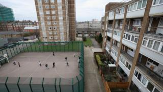 Children play a game of football in front of a residential development in the London borough of Tower Hamlets