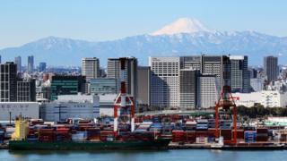Mount Fuji is seen behind an international cargo terminal in Tokyo
