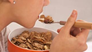 Mujer comiendo cereal.
