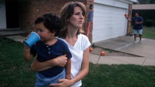 Una madre cargando a un niño en brazos.