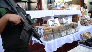 Armed agents of the Philippine Drug Enforcement Agency (PDEA) stand guard next to seized illegal drugs including bricks of cocaine