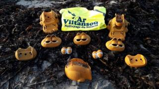 A collection of assorted Garfield phone fragments are shown arranged around some seaweed on the beach, with and Ar Viltansou high-viz vest visible