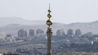 A general view of the mosque of the East Jerusalem neighbourhood of Issawiya and the Israeli West Bank settlement of Maale Adumim in the background, 19 November 2019