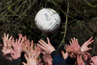in_pictures Competitors from the opposing teams, the Up'ards and the Down'ards, reach for the ball during the annual Royal Shrovetide Football Match in Ashbourne, northern England. 25 February 2020