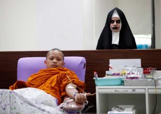 A Buddhist monk donates blood next to a staff member dressed in a nun horror costume during a Halloween blood donation drive at the National Blood Center of the Thai Red Cross Society in Bangkok, Thailand