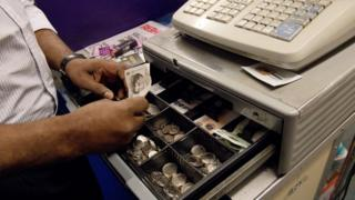 A worker takes payment for goods and puts the money in a cash register containing multiple denominations of pound coins and notes in a convenience store in London on October 7, 2016.