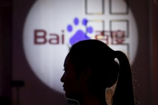 A woman is silhouetted against the Baidu logo at a new product launch from Baidu, in Shanghai, China, 26 November 2015