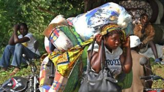 A refugee from the Democratic Republic of Congo (DRC) crosses the border into Uganda