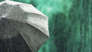 Open black umbrella in wet weather