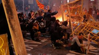 Protesters use fences as a barricade during clashes near police headquarters in Barcelona, on October 18, 2019
