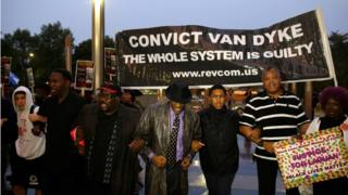 Protesters with sign saying CONVICT VAN DYKE