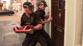 Police smash down a door during a morning raid in Lancaster