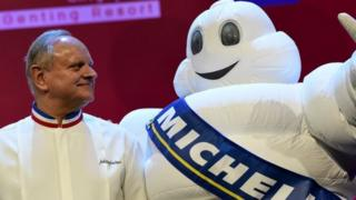 Joel Robuchon (L) stars poses with the tyre company's mascot during the Michelin Guides Award ceremony in Singapore on 21 July 2016
