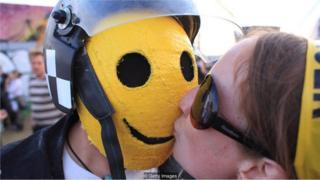 Mujer besa a hombre con máscara.