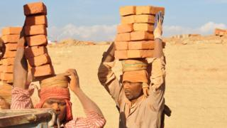 Workers carrying bricks