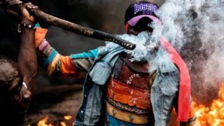 A man holds a burning stick as opposition supporters demonstrate at a burning barricade in Kibera, Nairobi, 25/10/2017