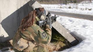 Female soldier fires gun