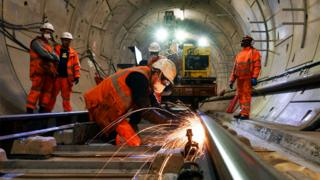 Construction workers on a section of train track inside a Crossrail tunnel, beneath Stepney in east London, in 2016