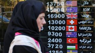 Iranians walk past a foreign exchange shop in Tehran on 22 April 2019