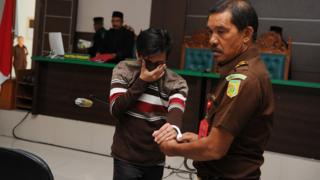 An Indonesian official (R) escorts a man (L) after his trial at a sharia court in Banda Aceh on May 17, 2017