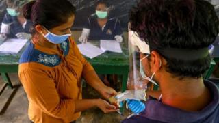 An election official sprays disinfectant on a voter during a mock election in Sri Lanka, 14 June 2020