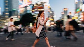فتاة تنظر إلى هاتفها المحمول وهي تسير في الشارع
