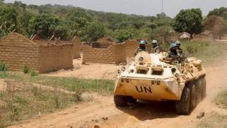 United Nations peacekeeping force vehicles drive by houses destroyed by violence in September, in the abandoned village of Yade, Central African Republic April 27, 2017