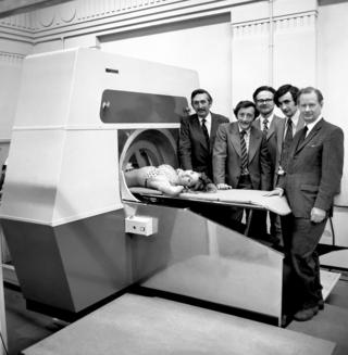Model Gillian Duxbury is seen with a CT scanner alongside Godfrey Hounsfield and other developers