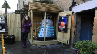 Museum co-owner Lisa Cole stands next to the Dalek and shed