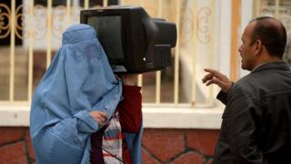 Афганская женщина продает телевизор в Мазари-Шарифе