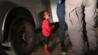 Una niña mira al agente de la Patrulla Fronteriza.