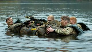 Soldiers swim across a lake on a previous march