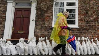 A woman walks past sand bag flood defences in the village of Naburn near York as water levels rose on the River Ouse.