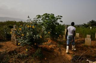 A graveyard worker with his back to the camera walks through Waterloo Ebola Graveyard. Sierra Leone.