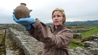 Curator of Roman collections Frances McIntosh, holding an infant's feeding bottle