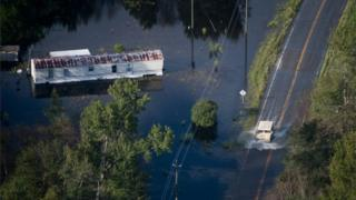 A truck drives through floodwaters