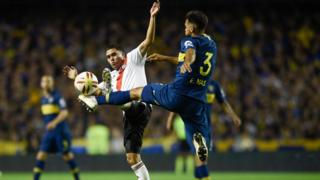 Players challenge a ball at a Boca v River match