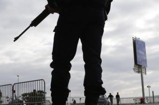 An armed French policeman stands guard at the Franco-Italian border in Menton