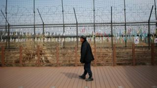 A man looks at the military wire fences attached with South Korean national flags at the Imjingak Pavilion near the border with North Korea, in Paju, South Korea, Friday, March 18, 2016.